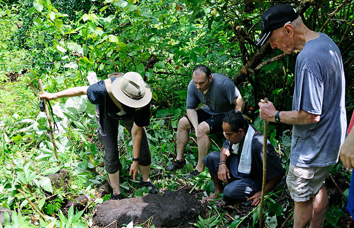 Hiking with Felicia Beardsley, archaeologist, who is showing us a stone carving found in the interior of Kosrae, FSM.